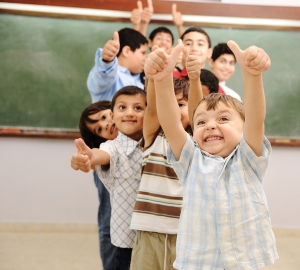 Kids in classroom thumbs up